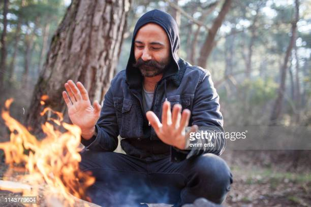 man warms himself at camp fire in the forest - ottoman empire stock pictures, royalty-free photos & images