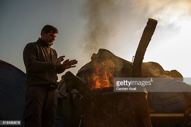 A man warms his hands by a fire at the Idomeni refugee camp on the Greek Macedonia border on March 19 2016 in Idomeni Greece Thousands of migrants...