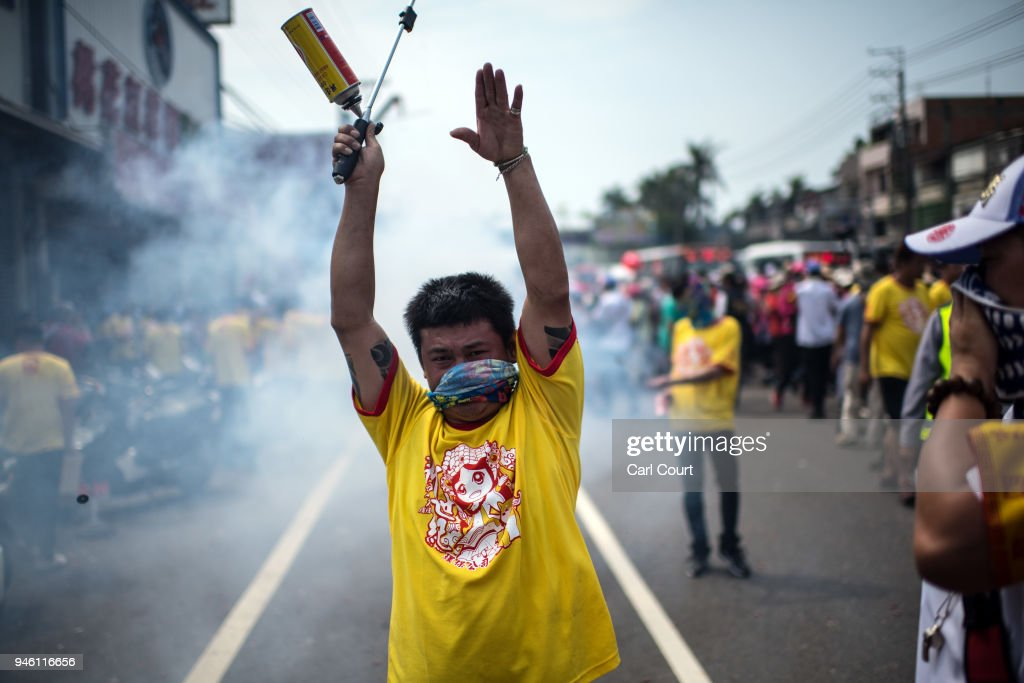 A man warns people that firecrackers are about to go off on day two of the nine day Mazu pilgrimage on April 14, 2018 in Dadu, Taiwan. The annual Mazu Pilgrimage begins at Jenn Lann Temple in Taichung and sees around 200,000 pilgrims walk up to 12 hours each day for nine days carrying a statue of Chinese sea goddess Mazu in a sedan chair. The journey covers around 350 kilometres, much of it through mountainous and rugged terrain and visits more than 100 temples before returning to Taichung. The centuries-old pilgrimage is now recognised by UNESCO as living heritage and with an estimated 5 million participants spread over the nine days, it is considered to be one of the greatest religious festivals in the world.