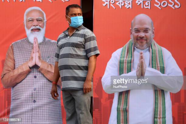Man warring protective face mask stand in front of India Prime Minister Narendra Modi and Union Home Minister Amit Shah big flex Photo Poster during...