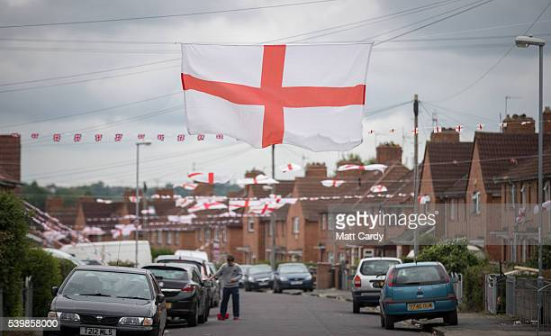 A man washes a car as houses in Torrington Avenue display England flags in support of the England football team on June 13 2016 in Bristol England...