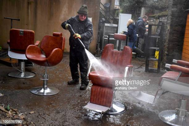 A man washes barber chairs as residents begin clearing up following severe flooding beside the River Calder on February 10 2020 in Mytholmroyd West...