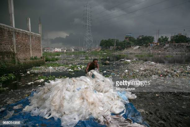 A man washes chemically treated plastic bags in a canal that leads to the Buriganga river on June 3 2018 in Dhaka Bangladesh Bangladesh has been...