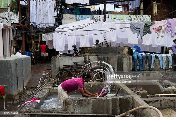 A man washes clothes at an openair laundromat near Cuffe Parade in South Mumbai