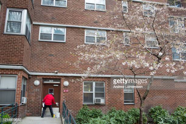 A man washes down the doorway of an apartment building on March 25 2020 in the Chelsea neighborhood of New York City