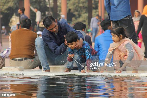 A man washes face of his kid before offering prayers near the pond in Jamia Masjid Old Delhi On Sunday10th of December 2017