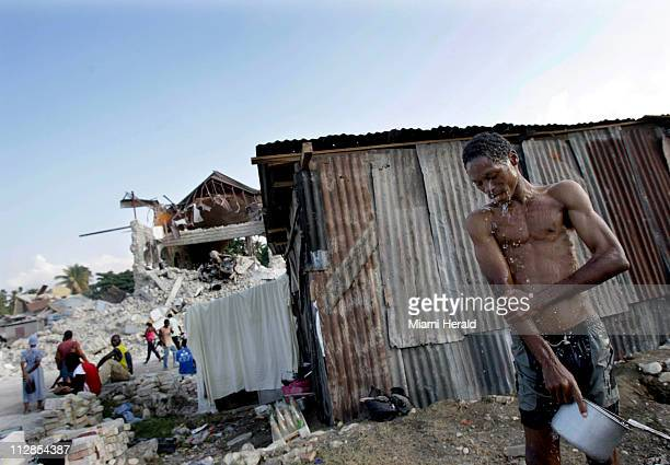 A man washes himself across from the demolished Sainte Rose de Lima Ccurch in Leogane Haiti Wednesday January 20 2010 The lot was set up to...