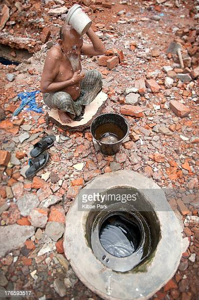 Man washes himself in a construction site: 1.8 billion people who have access to a water source within 1 kilometer, but not in their house or yard,...