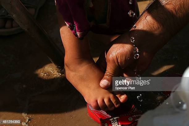 A man washes his daughters feet at a temporary displacement camp for Iraqis caughtup in the fighting in and around the city of Mosul on June 26 2014...