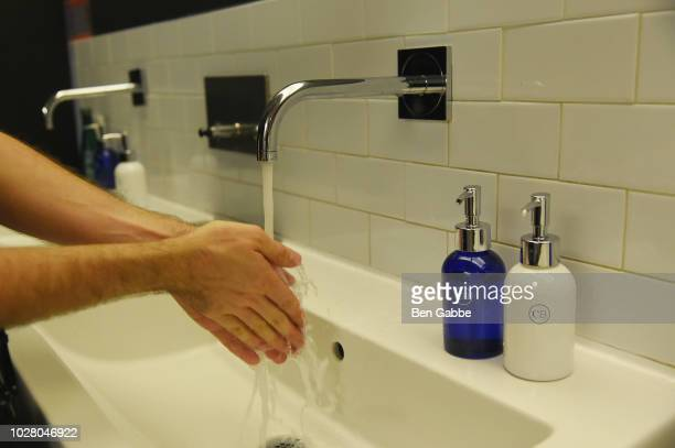 A man washes his hands with Capri Blue soap in the bathroom at New York Fashion Week The Shows Day 1 on September 6 2018 in New York City