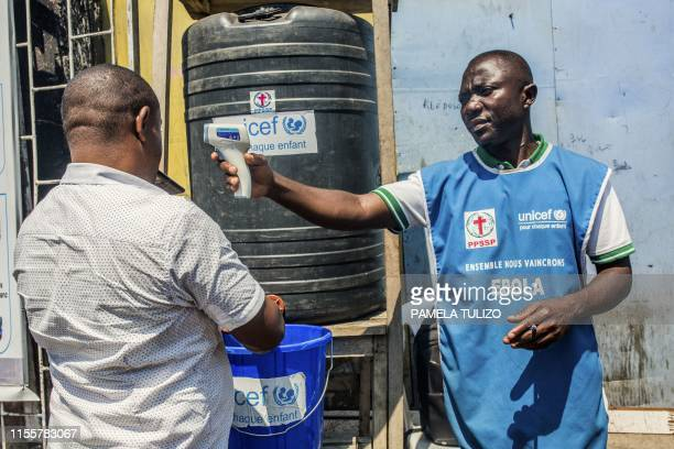 Man washes his hands with chlorine as a Unicef health worker holding a thermometer mans a washing station on July 15, 2019 in Goma. - Authorities in...