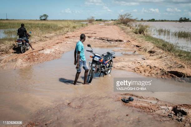 A man washes his motorbike on a road which destroyed by the Cyclone Idai in Tica Mozambique on March 24 2019 Cyclone Idai smashed into Mozambique's...