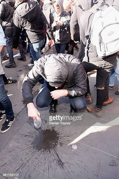 A man washes pepper spray from his face on July 18 2015 in Melbourne Australia 'Reclaim Australia' grassroots rallies are being held across Australia...