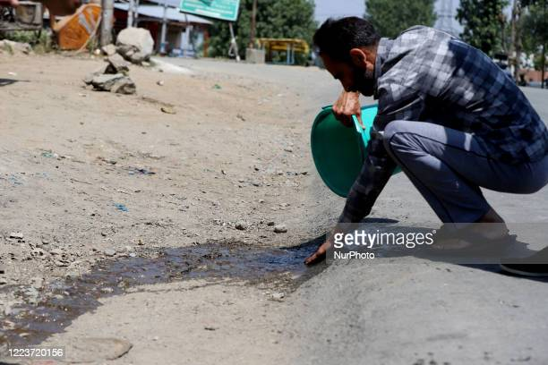 Man washes the blood near the shootout site after millitants attacked CPRF party in Sopore town of district baramulla Jammu and Kashmir, India on 01...