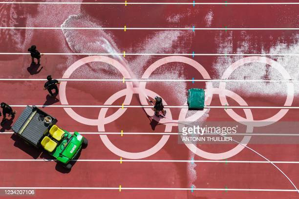 Man washes the track at the Olympic Stadium ahead of the athletics events of the Tokyo 2020 Olympic Games in Tokyo on July 26, 2021.