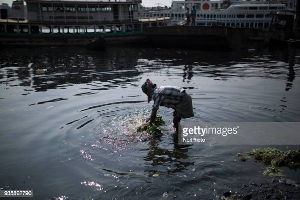 A man washes vegetable in polluted water in Buriganga river in Dhaka Bangladesh on March 21 2018