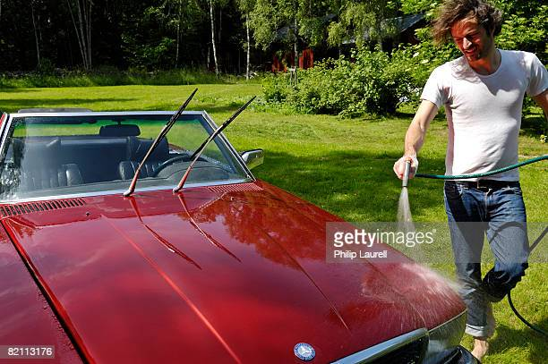 a man washing a car sweden. - red tube top stock pictures, royalty-free photos & images