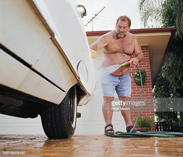 Man washing car in driveway, ground view