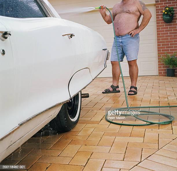Man washing car in driveway, low section