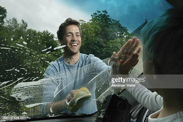 Man washing car looking at boy (3-5) in car through window, smiling