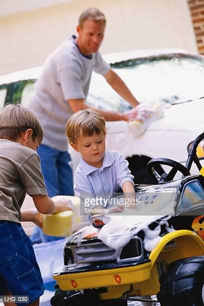 Man washing car; two boys washing toy car