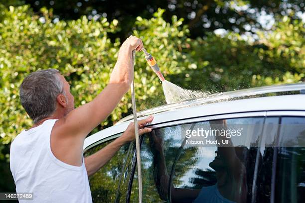 Man washing car with hose