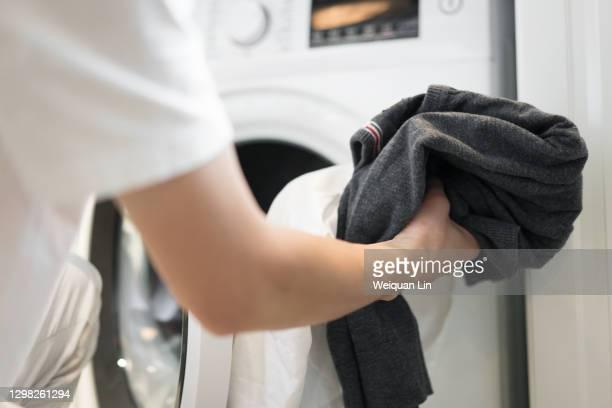 man washing clothes in washing machine - washing machine stock pictures, royalty-free photos & images