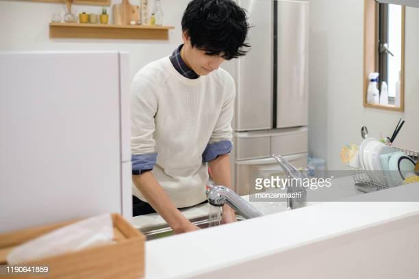 キッチンで皿を洗う男 - 洗う ストックフォトと画像