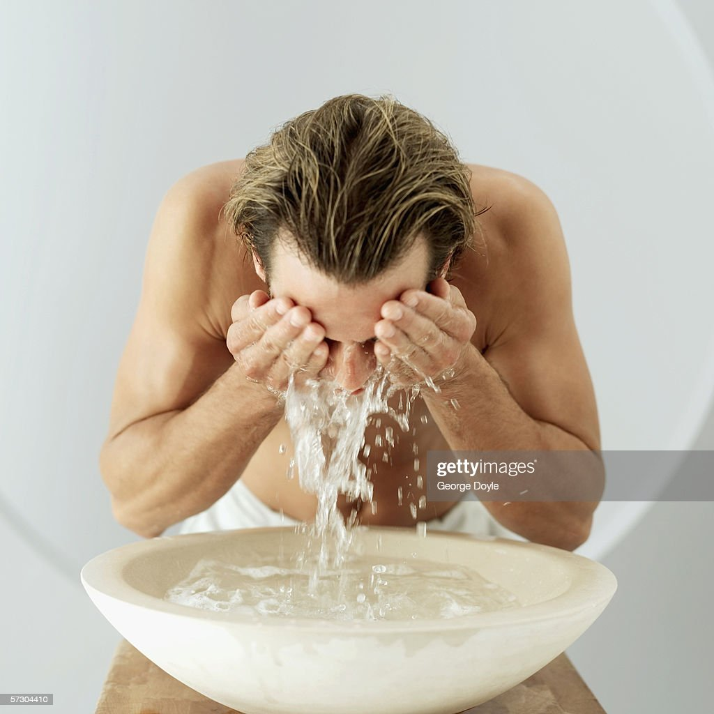 Man washing face at washbasin : Stock Photo