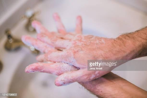 man washing hands, in between fingers, good hygiene, preventing spread of germs, bacteria and viruses - foam finger - fotografias e filmes do acervo