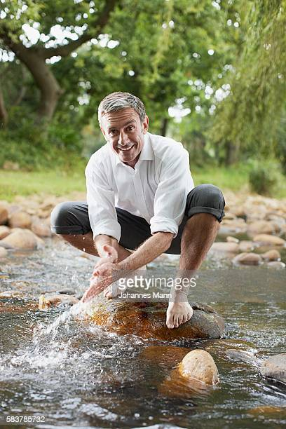 Man Washing Hands in Stream