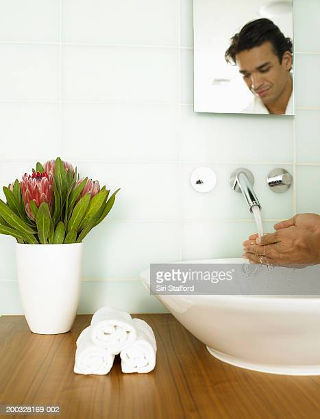 Man washing hands on sink, reflection in mirror