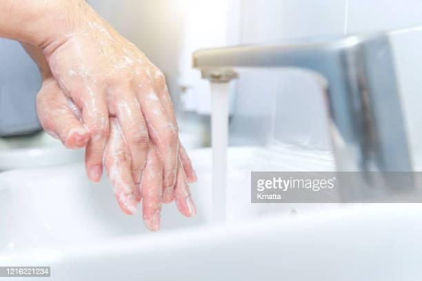man washing hands, preventing spread of bacteria and virus - foam finger - fotografias e filmes do acervo