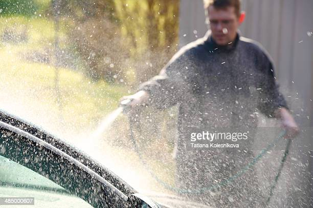 Man washing his car in front of his house