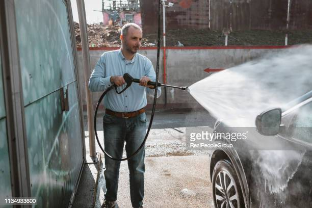 man washing his car with high-pressure washing - car wash brush stock photos and pictures