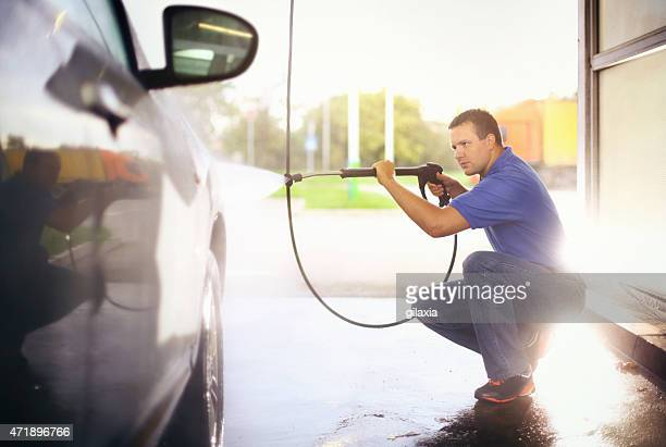 Man washing his car with hose sprayer.
