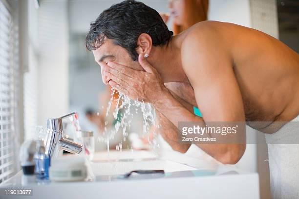 Man washing his face in bathroom