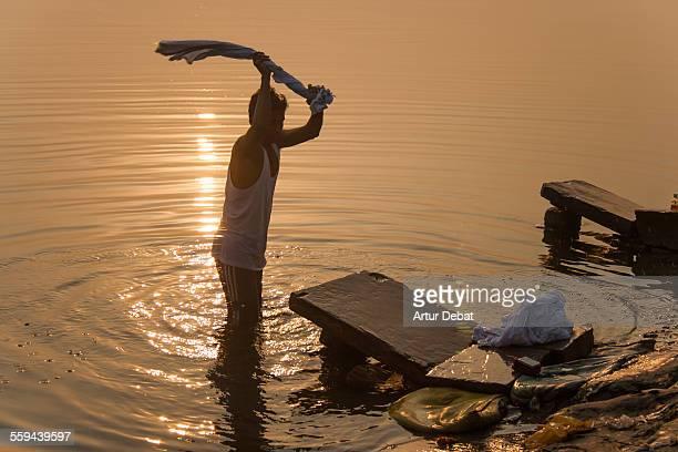 Man washing his laundry on the Ganges shoreline during the sunrise in Varanasi India Asia
