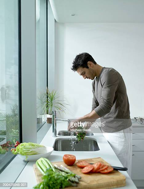 Man washing parsley at kitchen sink, side view