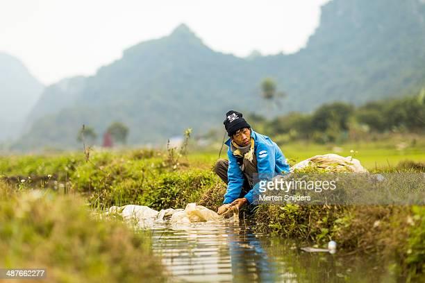 Man washing plastic sheet in stream