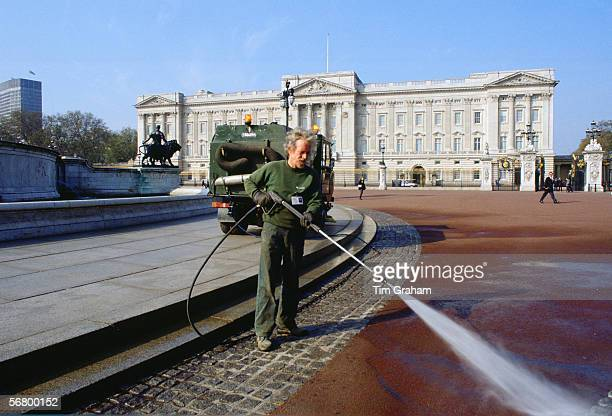 Man washing the road outside Buckingham Palace to prepare for a forthcoming State Visit.