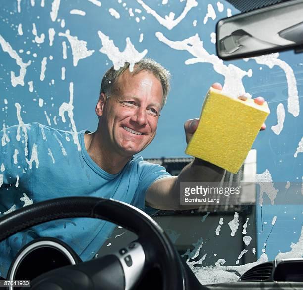 Man washing window of car