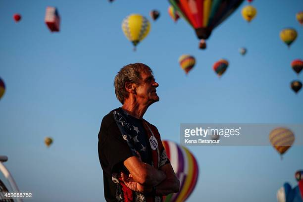 A man watch hot air balloons flying across the sky during the 32nd annual QuickChek New Jersey Festival of Ballooning on July 25 2014 in Readington...