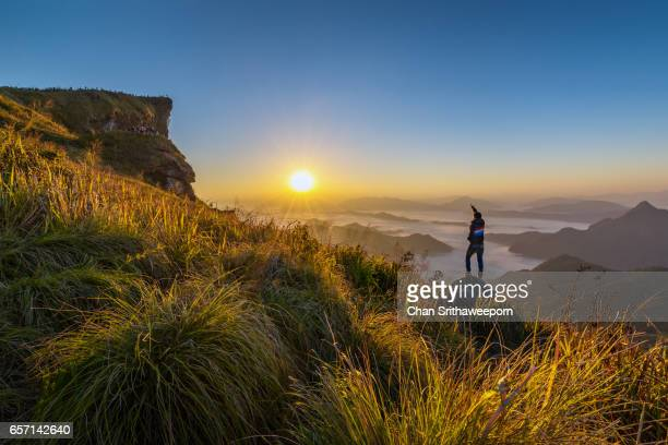 A man watch the sunrise in the most beautiful time at Phu chi fah , Chiangrai , Thailand