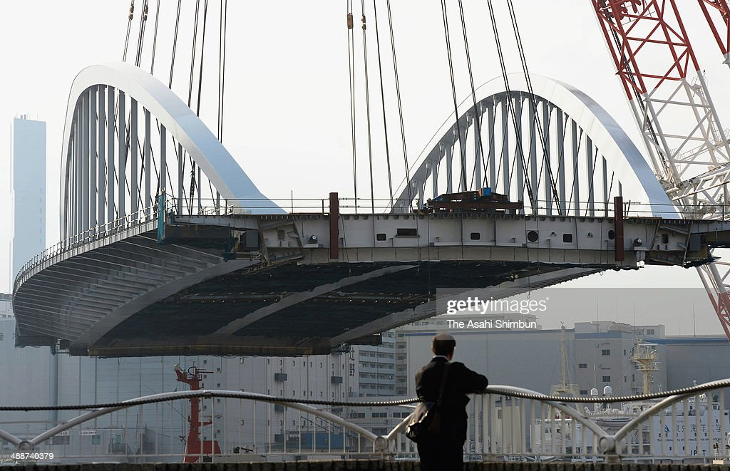 A man watches a 2,600-ton new bridge is lifted by a huge crane on May 8, 2014 in Tokyo, Japan. The 120-meter bridge, assembled at Yokohama Port not to disturb the traffic of the Sumida River, will be part of Loop Line 2 which is an expected major traffic artery linking major venues at the 2020 Tokyo Summer Olympics.