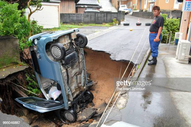 A man watches a car falling in a sinkhole on July 8 2018 in Otsuki Kochi Japan At least 81 people were killed and 87 missing The deluge triggered by...
