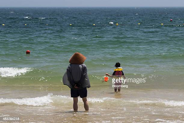 A man watches a child standing in the sea at Haeundae beach in Busan South Korea on Friday July 31 2015 South Korea urged its people to put the...
