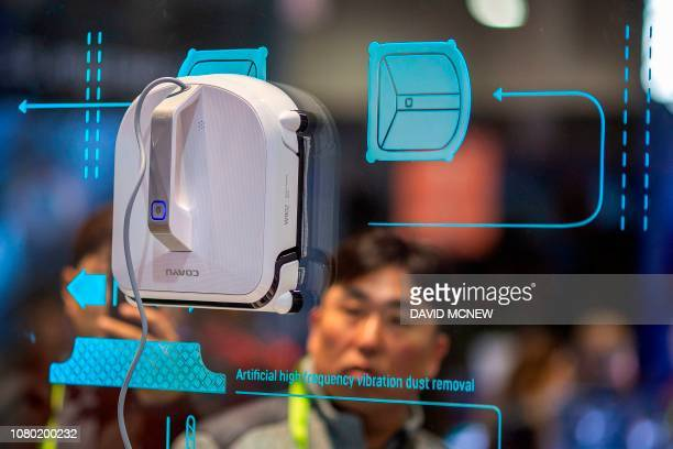 A man watches a Coayu W902 window cleaning robot at the Las Vegas Convention Center during CES 2019 in Las Vegas on January 10 2019