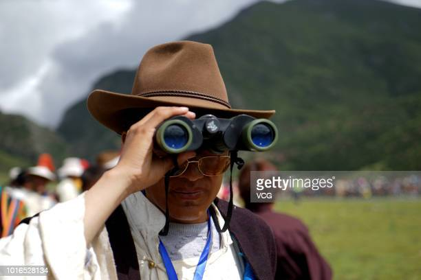 A man watches a horse race during a horse racing festival with a telescope at Damxung County on August 9 2018 in Lhasa Tibet Autonomous Region of...