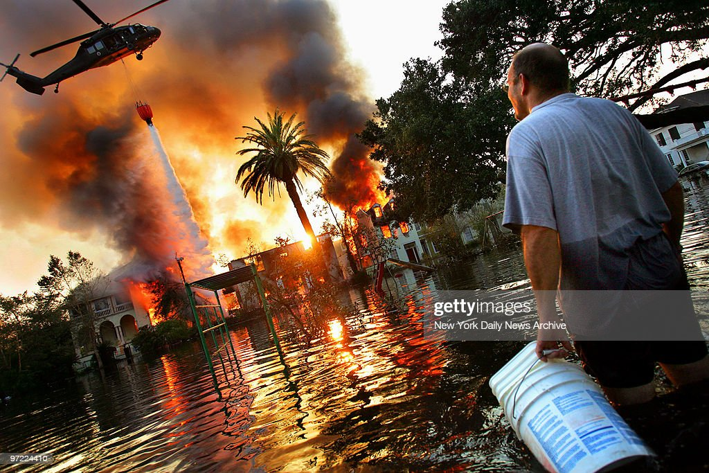 A man watches a house burn on Napolean St. as helicopters try to extinguish the fire by dropping water from above in Hurricane Katrina ravaged New Orleans. Because of the extensive flooding caused by the breaking of the city's levies, fire trucks were unable to reach burning homes and in some cases whole blocks burned to the ground.